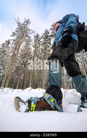 Close up of hiker wearing snowshoes on feet while snowshoeing in forest in deep powder snow in winter - Stock Photo