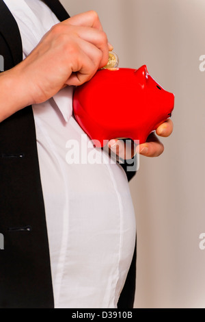 Pregnant Business Woman throws two euro in piggy bank - Stock Photo