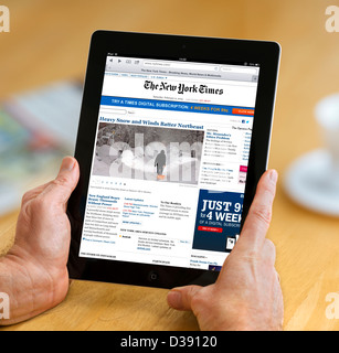 Reading the online edition of the New York Times viewed on a 4th generation Apple iPad, USA - Stock Photo
