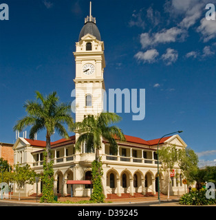 Historic ornate post office with clock tower and arched colonnade and palm trees in the Queensland city of Bundaberg - Stock Photo