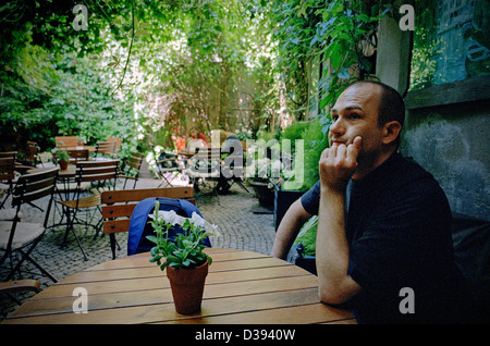 Poznan, Poland, a man sitting in the garden of a cafe and waiting - Stock Photo