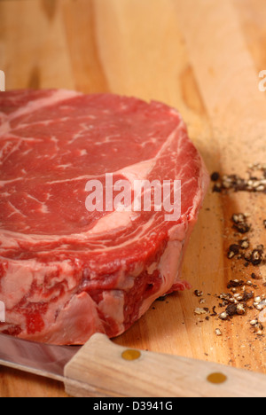A rib eye steak with cracked black pepper and a knife - Stock Photo