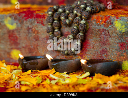 Oil Lamps and Indian Rudraksha / Japa Mala prayer beads on the steps of a rural indian village shrine / temple. - Stock Photo