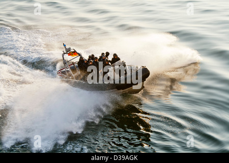 A SWAT -special forces police- inflatable rigid hull (zodiac type) boat hitting the wake of a ship and creating - Stock Photo