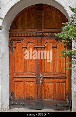 beautiful wooden double doors, in a rustic setting with stucco building in an archway. Architectural element. - Stock Photo