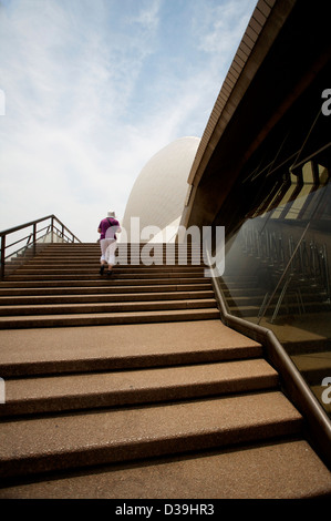 A man climbing the stone stairs outside The Sydney Opera House performing arts centre in Sydney, New South Wales, - Stock Photo
