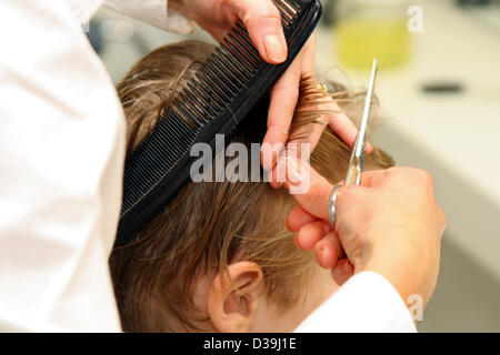 (dpa) - A hairdresser cuts the hair of a young boy at a hairdresser's shop in Frankfurt , Germany, 05 May 2005. - Stock Photo
