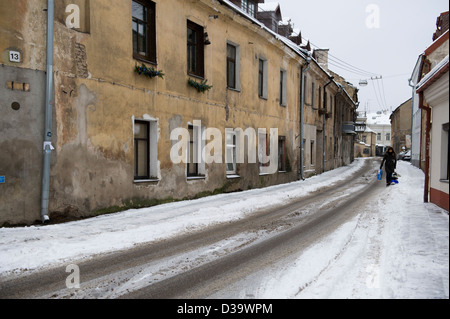A woman pulling a child along on a sled in the snowy streets of Vilnius - Stock Photo