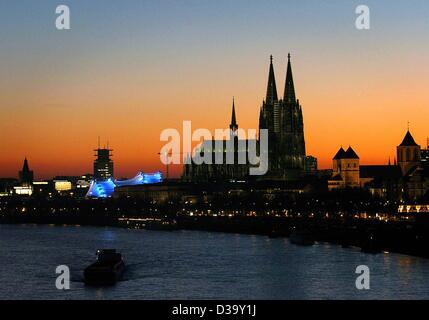 (dpa) - A river boat travels up the River Rhine passing the city of Cologne which is cast in in the red light of - Stock Photo