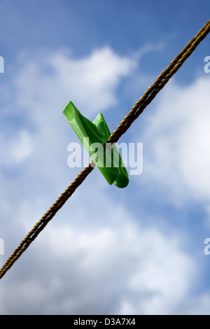 A single green clothes peg or pin on a washing line, against a cloudy blue sky. - Stock Photo