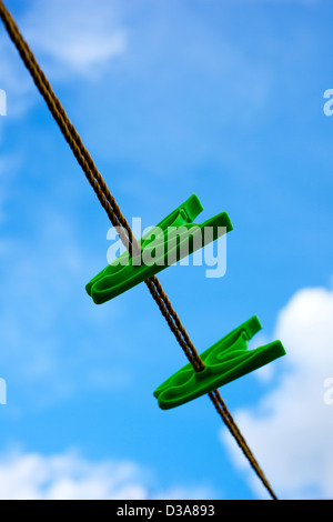 Two green peg on a washing line, against a cloudy blue sky. - Stock Photo