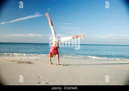 Woman doing cartwheels on tropical beach - Stock Photo