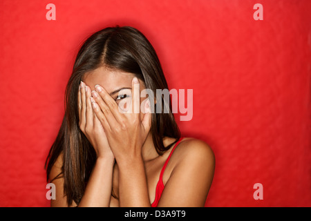 Portrait of cute Chinese Asian / Caucasian playful shy woman hiding face laughing timid isolated on red background - Stock Photo