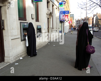 united kingdom west london acton high street a muslim woman using an atm - Stock Photo