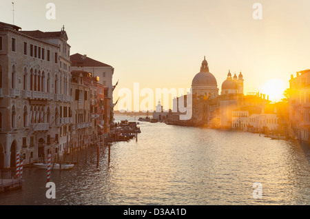 Sun setting over city buildings on canal - Stock Photo