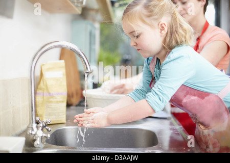 Girl washing her hands in kitchen - Stock Photo