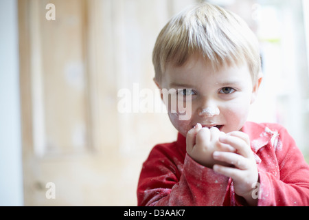 Boys face covered in flour in kitchen - Stock Photo