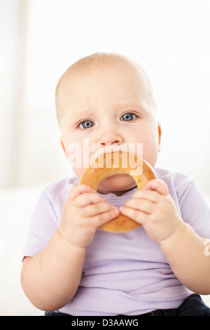 Baby girl eating bagel - Stock Photo