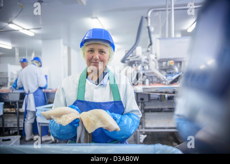 Portrait of worker holding fresh fish fillets in food factory - Stock Photo