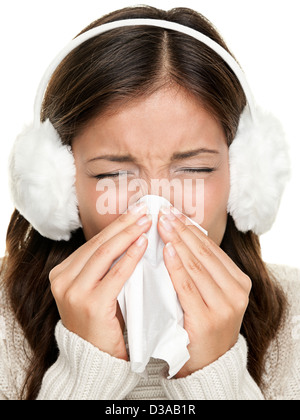 Sneezing woman sick blowing nose. Young woman being cold wearing earmuffs and sweater. Asian Caucasian female model - Stock Photo