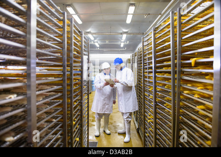 Workers checking details on tablet of fish for smoking in food factory - Stock Photo
