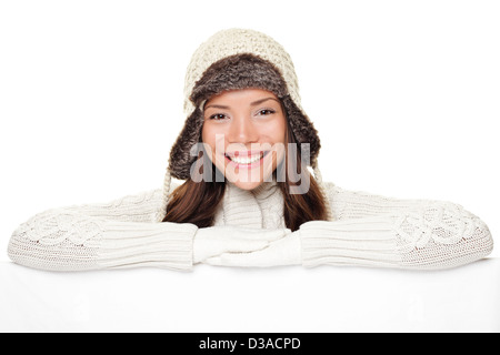 Portrait of cute smiling woman in warm winter sweater and wool cap showing blank white paper poster isolated on - Stock Photo