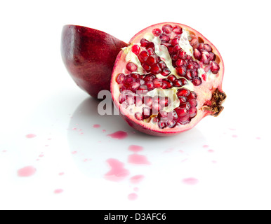 two half of pomegranate with juice droplets on white background - Stock Photo