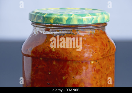 Spicy pepper sauce in preserving jars, chutney - Stock Photo