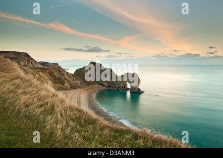 Durdle Door, a natural rock arch, on the Jurassic Coast in Dorset UK photographed just before sunset in January - Stock Photo