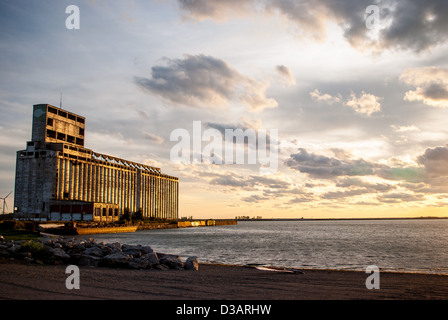 Photograph of an abandoned grain elevator near Buffalo New York at sunset with an industrial shore in foreground. - Stock Photo
