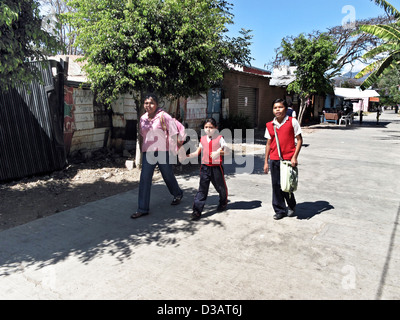 Mexican mother with small daughter & tween son dressed in school uniforms walking home from school on sunny day - Stock Photo