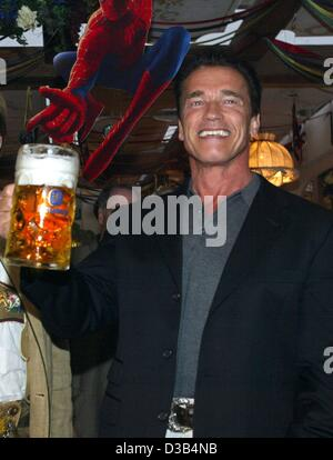(dpa) - Austrian Hollywood star Arnold Schwarzenegger holds up a mug of beer, which seems to be grabbed by a paper - Stock Photo