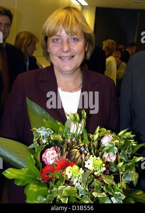 (dpa) - Angela Merkel, chairwoman of the CDU and newly elected leader of the CDU fraction in the Bundestag, holds a bouquet of flowers and smiles at the photographers, Berlin, 24 September 2002. 214 MPs of the CDU/CSU fraction voted for the 48-year-old, 18 voted 'no', eleven votes were invalid. Ange