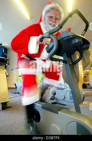 (dpa) - A man dressed as Santa Claus works out in a gym in Berlin, 18 Novemeber 2002. Santa needs to get fit for - Stock Photo