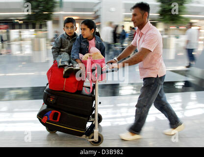 (dpa) - The picture shows the siblings Melisa and Tolbahan with their father rushing through the airport in Duesseldorf, - Stock Photo