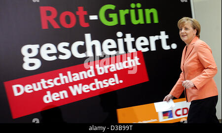 (dpa) - Chairwoman of the CDU Angela Merkel passes an election poster of the CDU in Berlin, Germany, 05 July 2005. Merkel commented on the recently released election manifesto of the SPD for the expected general election in September.