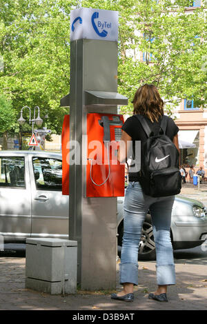 (dpa) - A young woman uses a public pay phone by telecommunications company ByTel in Frankfurt, Germany, 30 June - Stock Photo