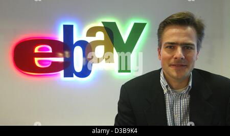 (dpa) - Philipp Justus, CEO of the online auction service 'ebay Deutschland', sits in front of the company's logo - Stock Photo