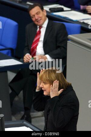 (dpa) - CDU chairwoman Angela Merkel gestures as she speaks in the Bundestag (lower house of German parliament), watched by Chancellor Schroeder, Berlin, 4 December 2002. Merkel said Schroeder was not fit for the neccessary tasks.