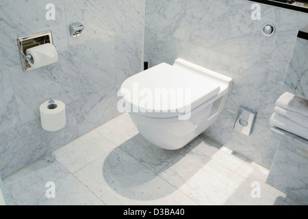 Smart wall mounted toilet in marble bathroom - Stock Photo