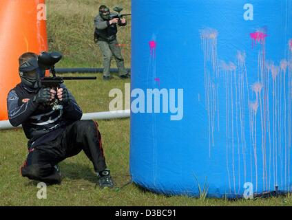 (dpa) - Paintball players take cover as they fire at enemies during a paintball competition in a forest near Frankfurt - Stock Photo