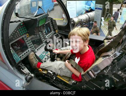 (dpa) - Four-year-old Theo sits in the pilot's seat in the cockpit of a Eurofighter during the Open Day at the Defence - Stock Photo