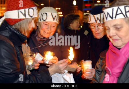 (dpa) - Protesters wear headbands with the writing 'no war' and light candles during a demonstration against a possible - Stock Photo
