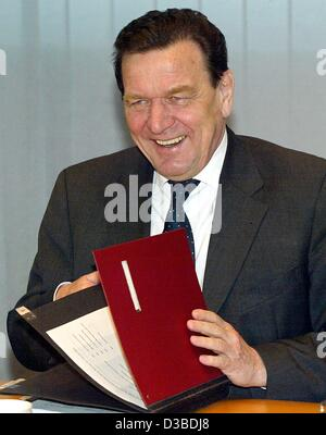 (dpa) - German Chancellor Gerhard Schroeder laughs as he opens a folder during a meeting in Berlin, 27 January 2003.