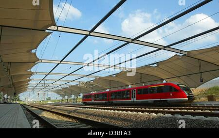 (dpa) - A passenger train of the Deutsche Bahn departs from a platform of the new train station at the airport Leipzig/Halle - Stock Photo