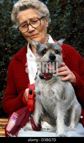 (dpa files) - An elderly woman sits on a bank with her dog on her lap in Berlin, Germany, September 2001. Many detached - Stock Photo