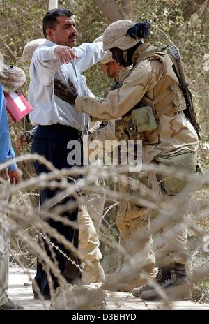 (dpa) - A US army soldier searches an Iraqi man in front of the main entrance of Hotel Palestine in Baghdad, 15 - Stock Photo