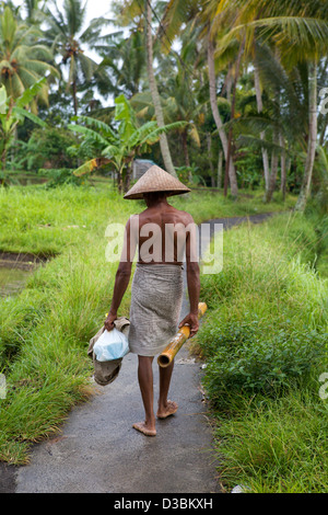 Balinese man walks barefoot through palm trees wearing only a sarong and traditional conical hat in Ubud Bali Indonesia - Stock Photo