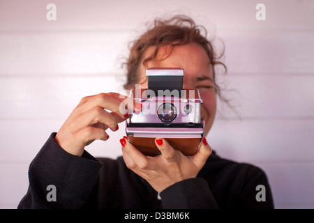 Girl taking a photograph with a Polaroid camera. - Stock Photo