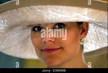 (dpa) - Crown Princess Victoria of Sweden smiles from underneath an elegant hat during a gala dinner for a state - Stock Photo